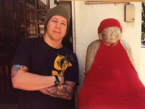 author derek vasconi standing next to the jizo statue at hiroshima